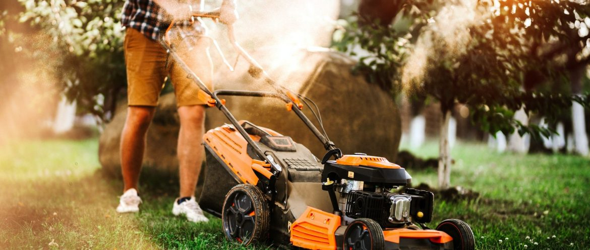 industrial lawnmower during summer sunset. Close up details of landscaping and gardening.